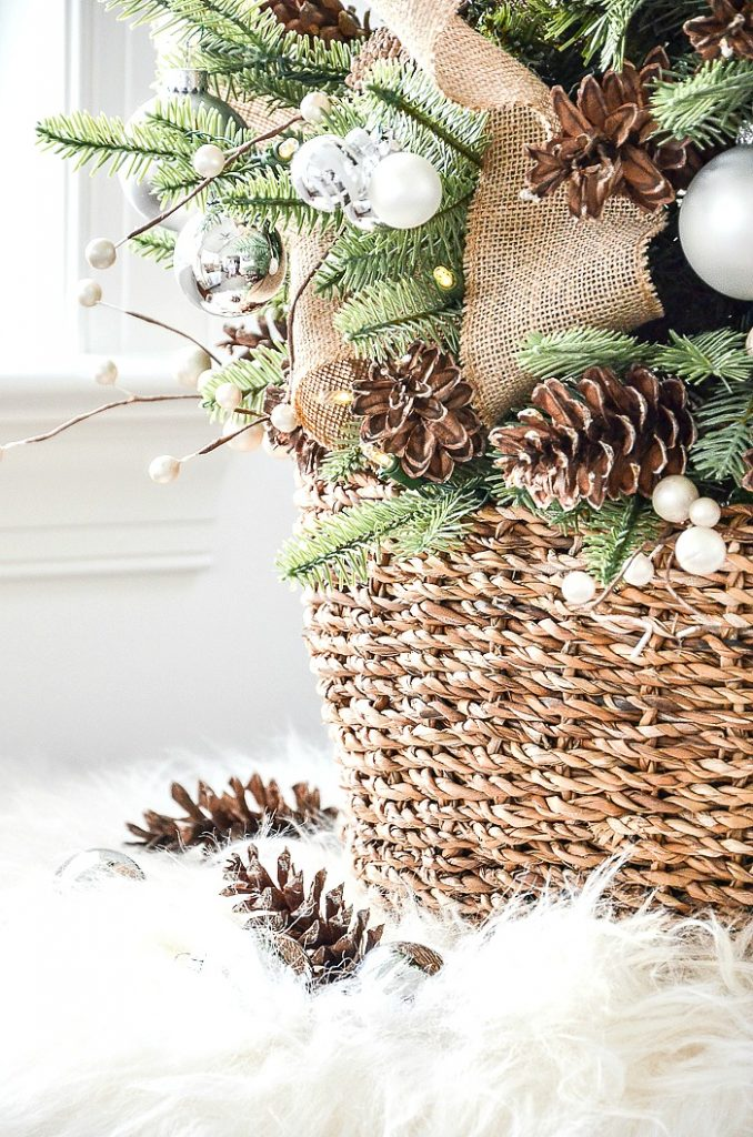 basket with tabletop christmas tree and pinecones