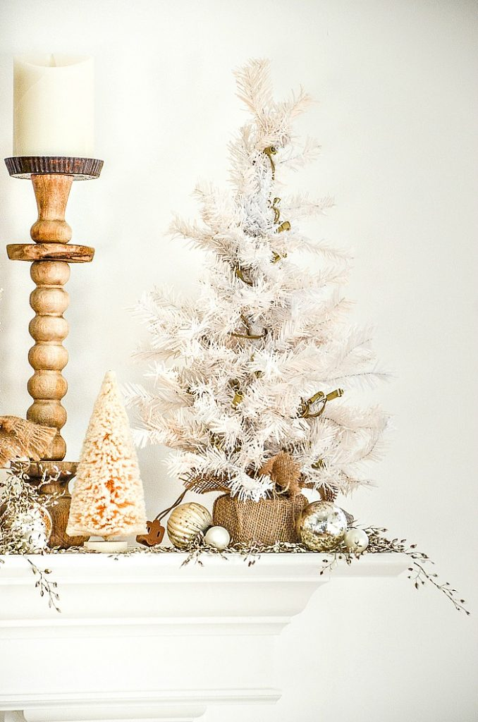 tall wooden candlesticks and tiny white trees on mantel