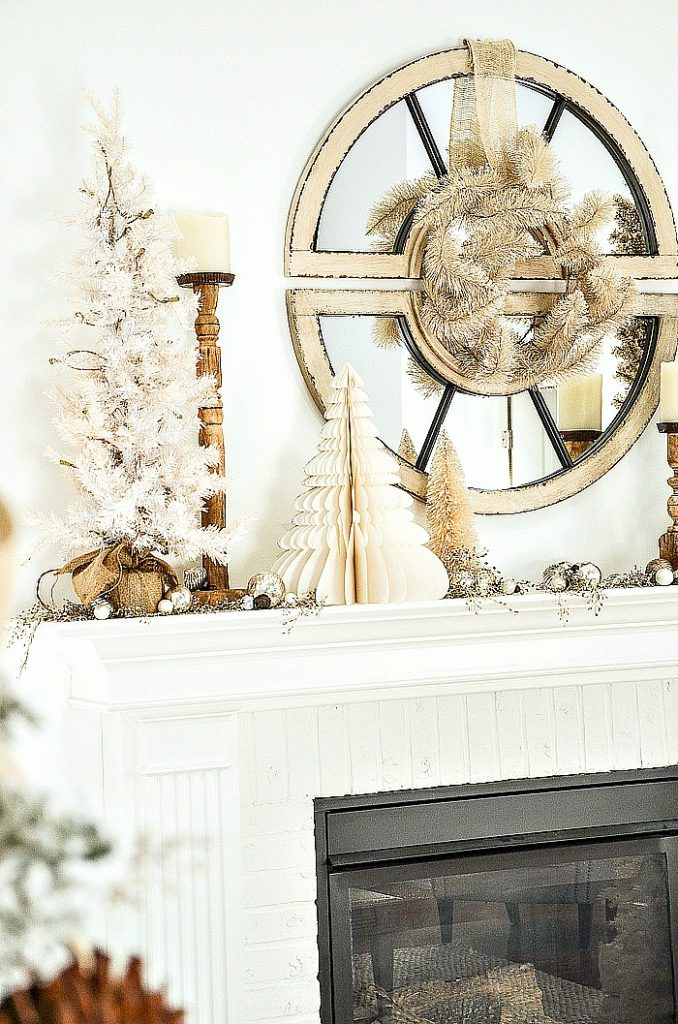 round mirror above a mantel decorated for Christmas