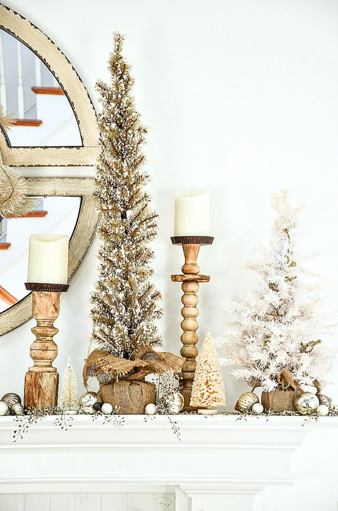 trees and candlesticks on a Christmas mantel