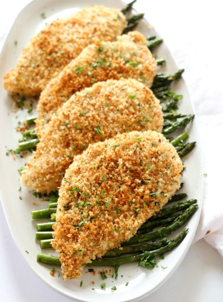 chicken cutlets under a bed of roasted asparagus