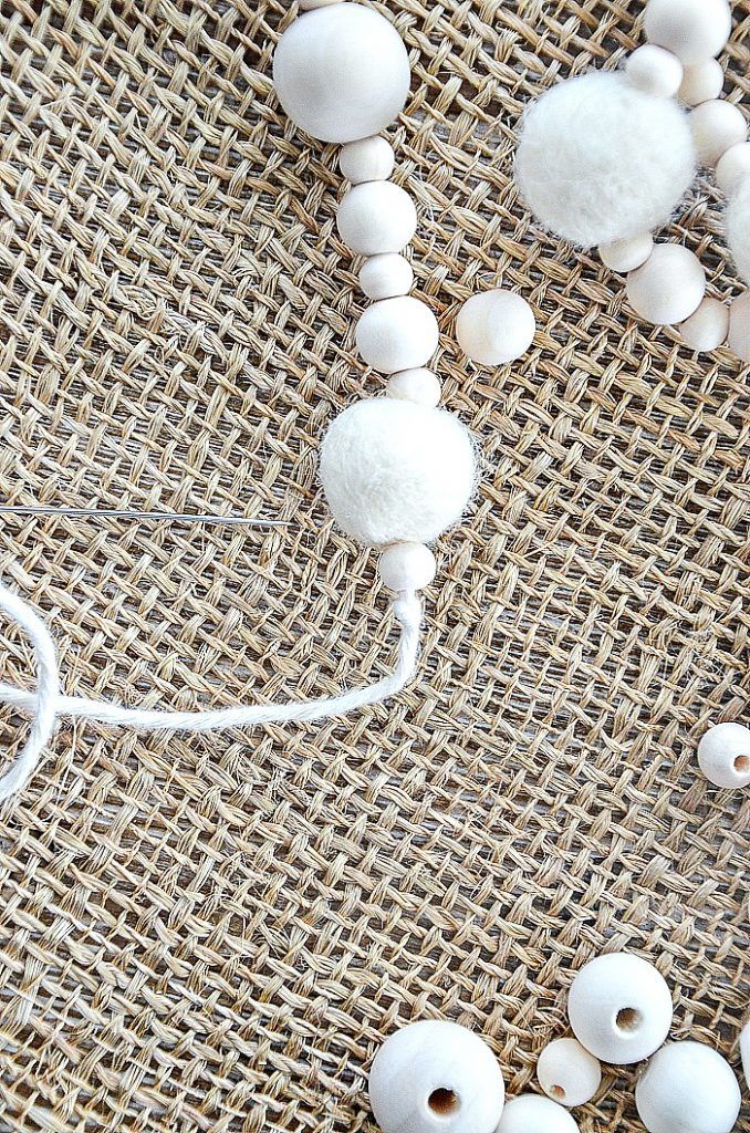 threading the beads and wool balls on twine to make a garland