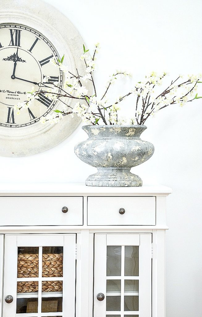 big gray urn on a white buffet filled with spring blooming branches
