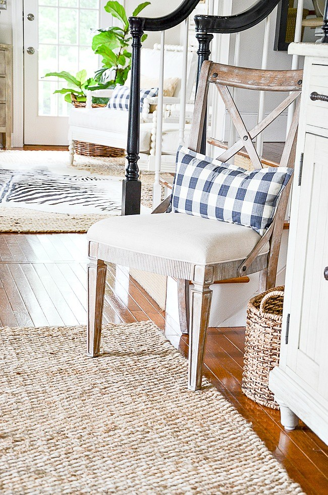 chair with a black and white buffalo check lumbar pillow on it