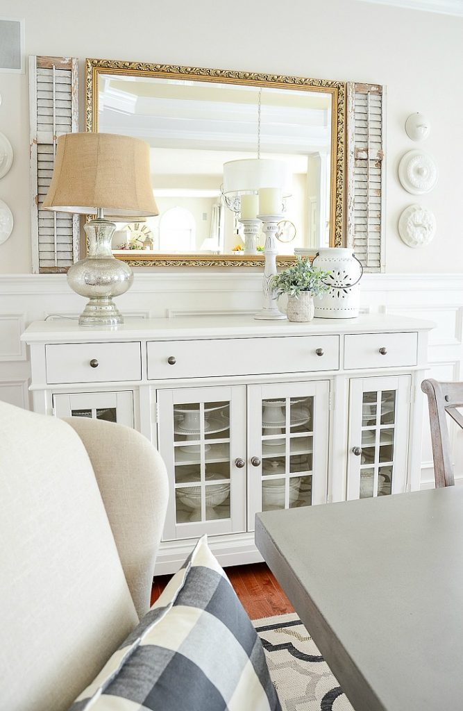 dining room with large white buffet and a gold mirror