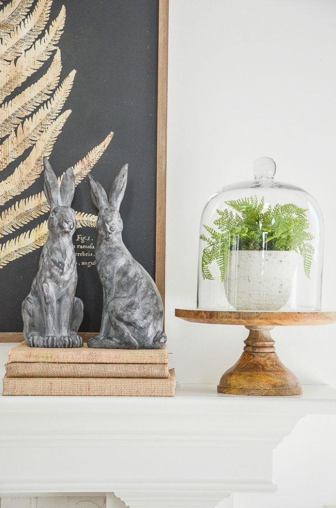 A MANTEL WITH TWO SOAPSTONE RABBITS ON BURLAP BOOKS