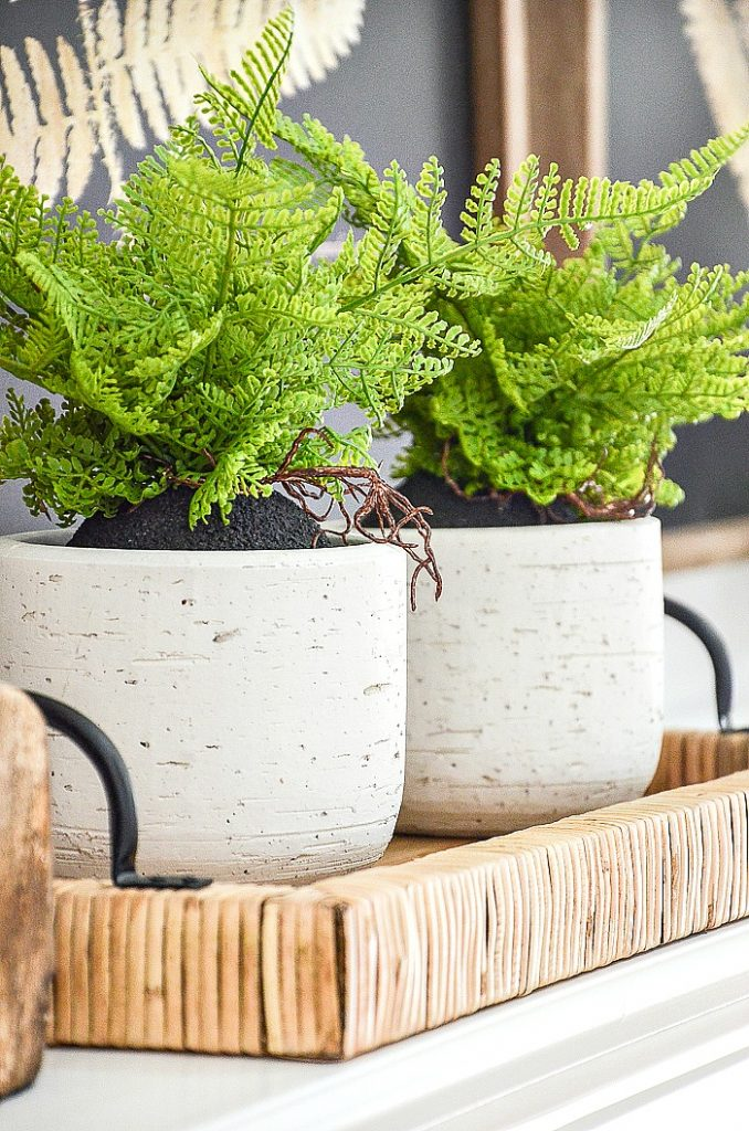 white pots filled with faux green fern plants on a spring mantel