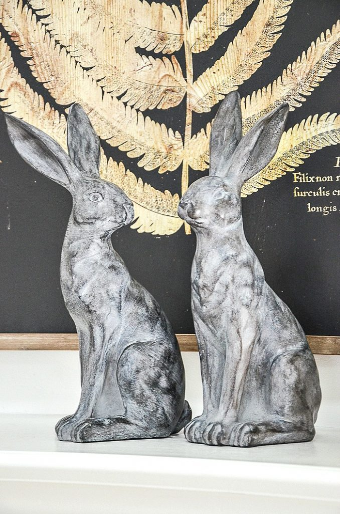 a pair of tall handsome soapstone rabbits sitting on a mantel
