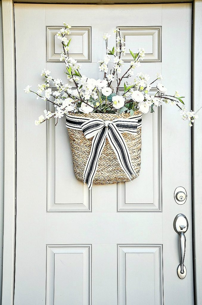 FRONT DOOR WITH A BASKET OF FLOWERS ON IT
