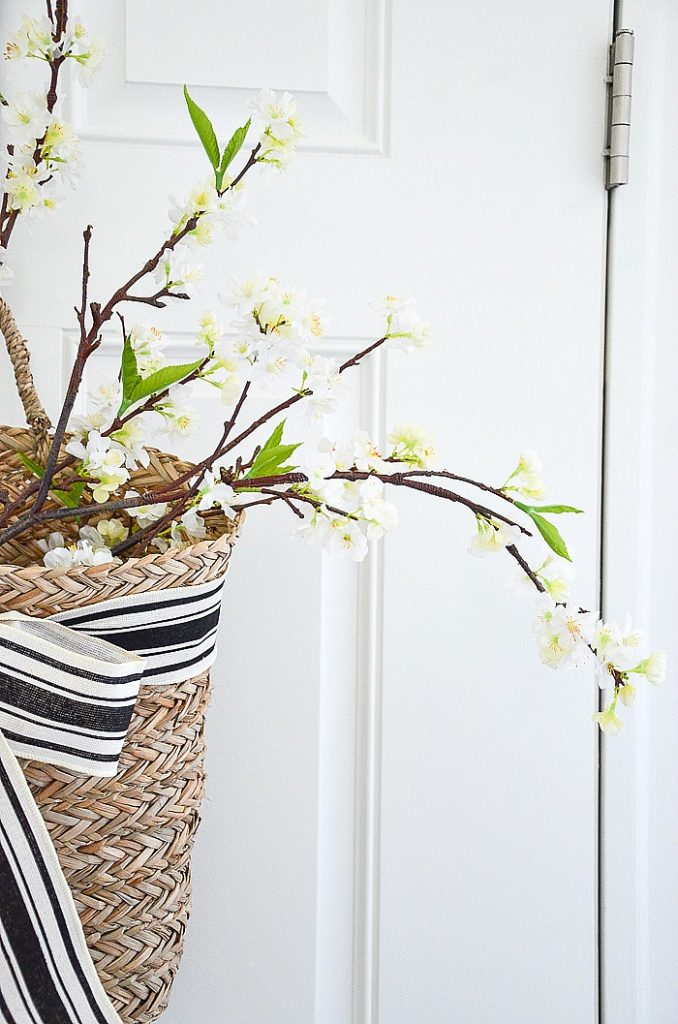 BASKET ON A DOOR FILLED WITH FAUX WHITE APPLE BLOSSOMS