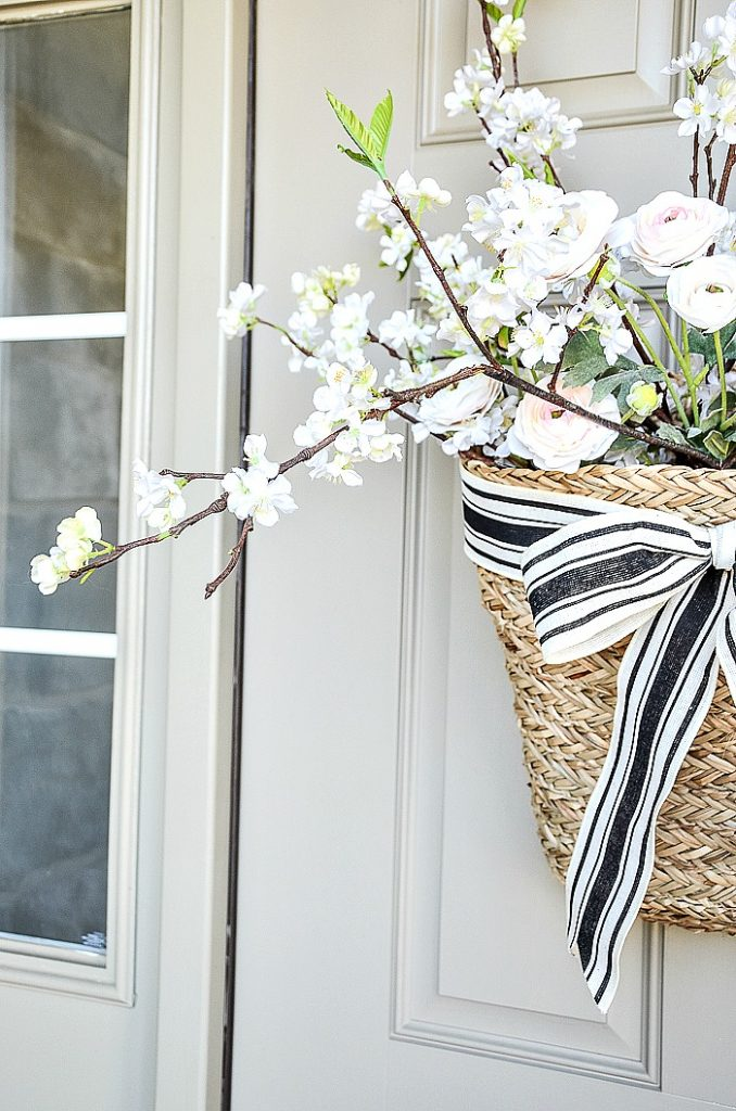 BASKET FILLED WITH FLOWERS HANGING ON A FRONT DOOR