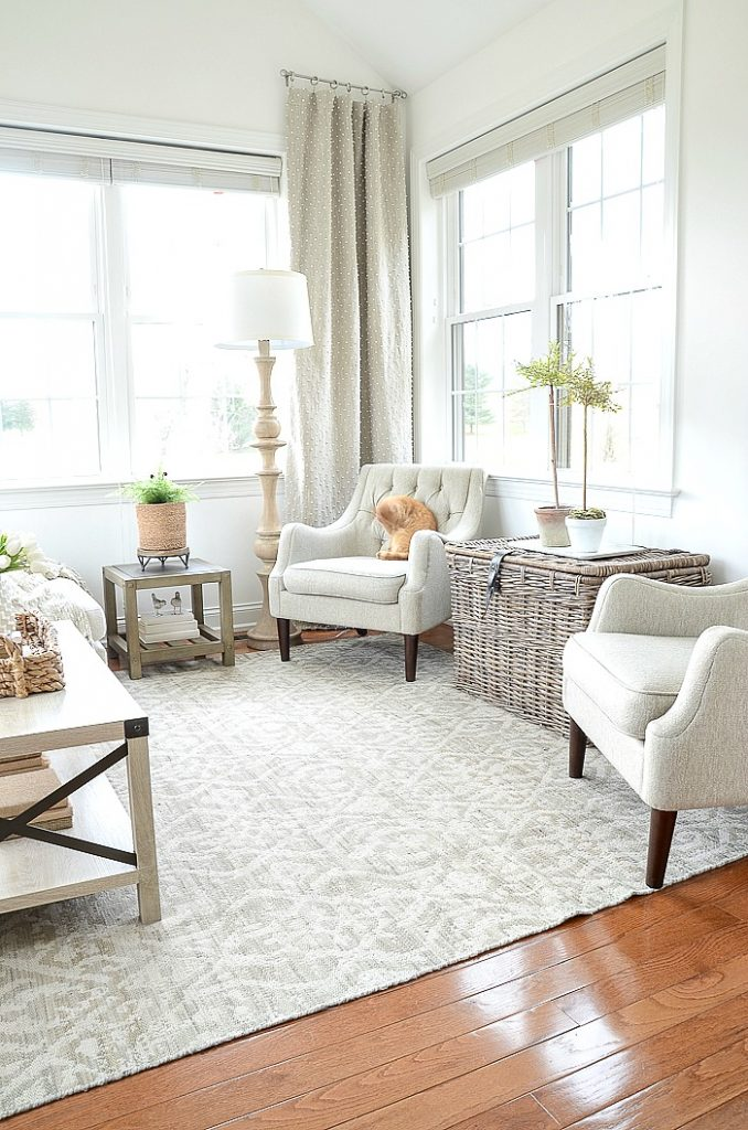 small sunroom decorated with neutral furnishings