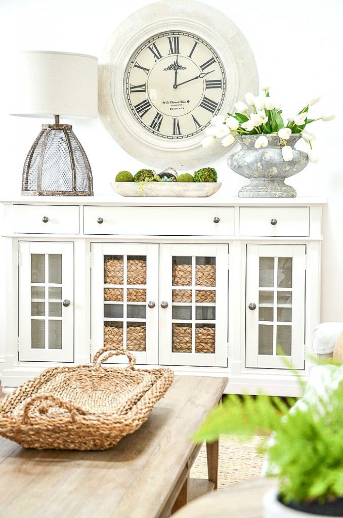WHITE BUFFET WITH BIG CLOCK AND AN URN OF SPRING TULIPS