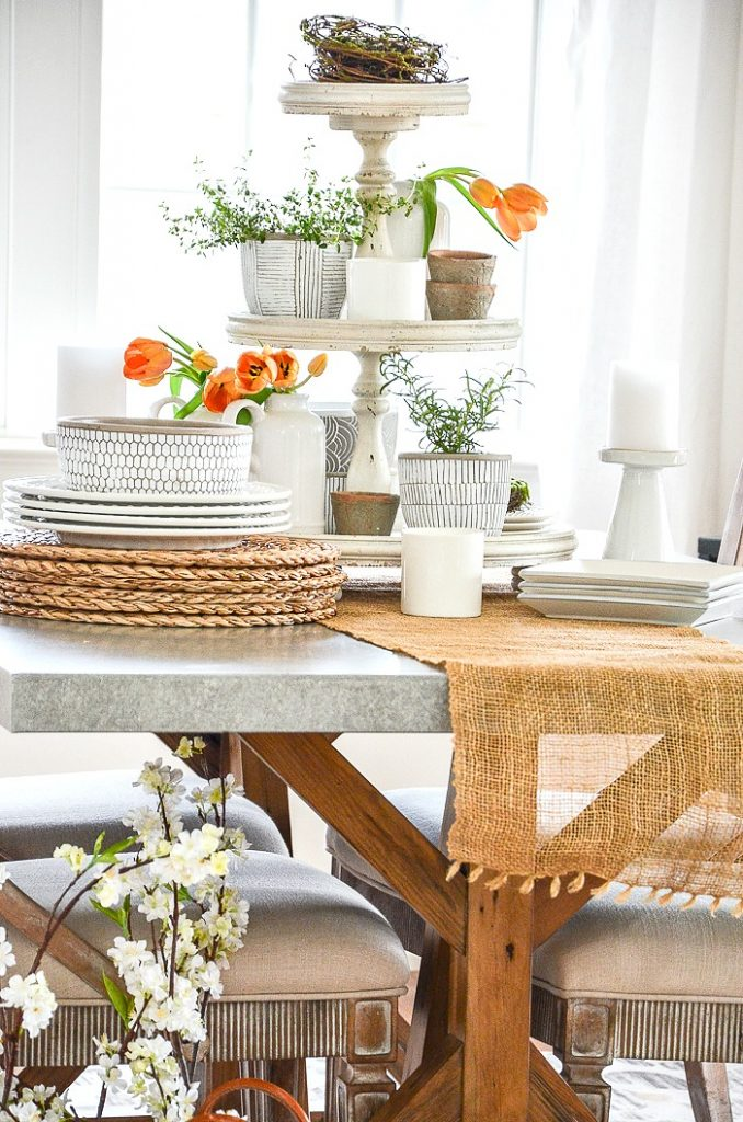 DINING TABLE WITH A TIERD TRAY FULL OF SPRING THINGS AND PLANTS