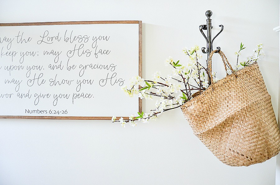 SCRIPTURE VERSE IN A FRAME HANGING IN THE ENTRYWAY OF A HOUSE DECORATED FOR SPRING