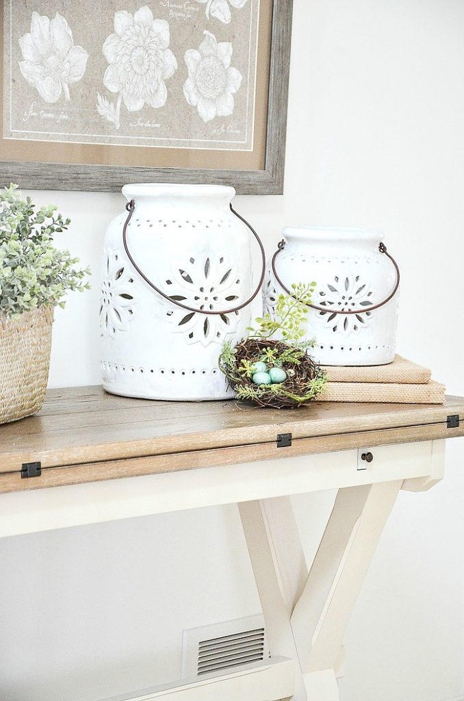 TWO WHITE  CERAMIC LANTERNS WITH A NEST IN FRONT OF THEM
