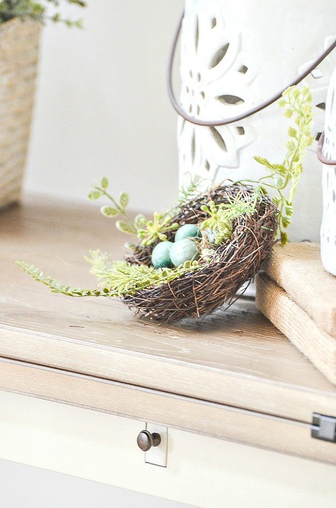 LITTLE NEST WITH BLUE EGSS IN IT ON A TABLE