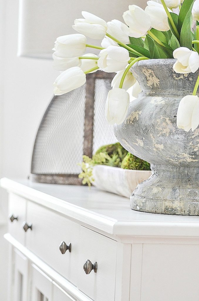 gray urn filled with white tulips on a spring house tour