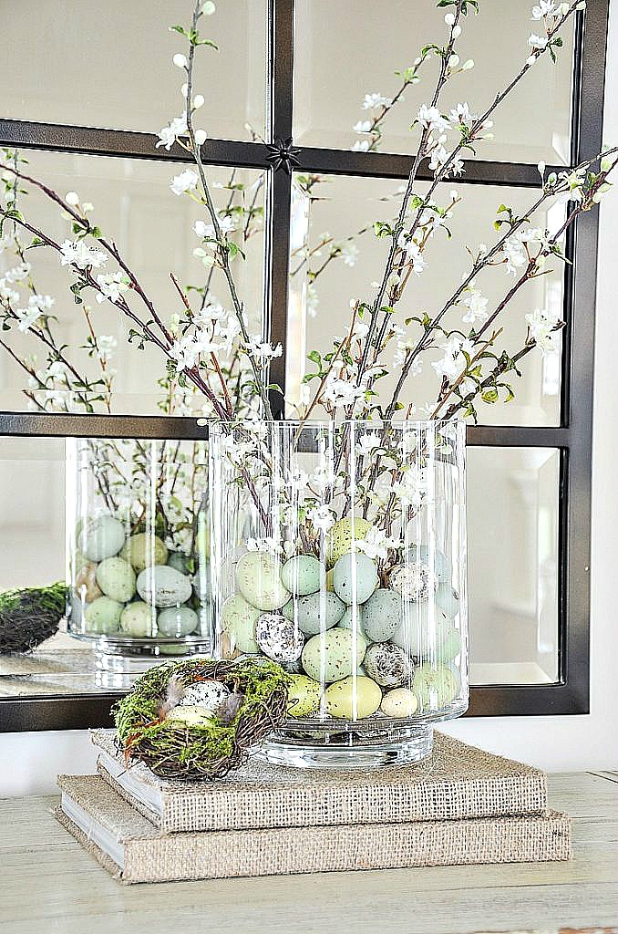 clear cylinder filled with pretty speckled eggs and spring flowering branches