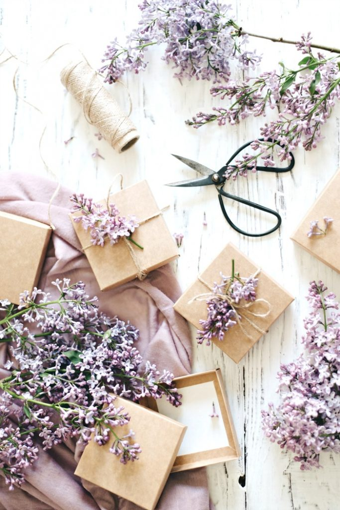 LILACS AND PACKAGES WRAPPED IN BROWN PAPER