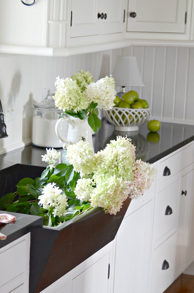 WHITE HYDRANGEAS IN A SOAPSTONE SINK