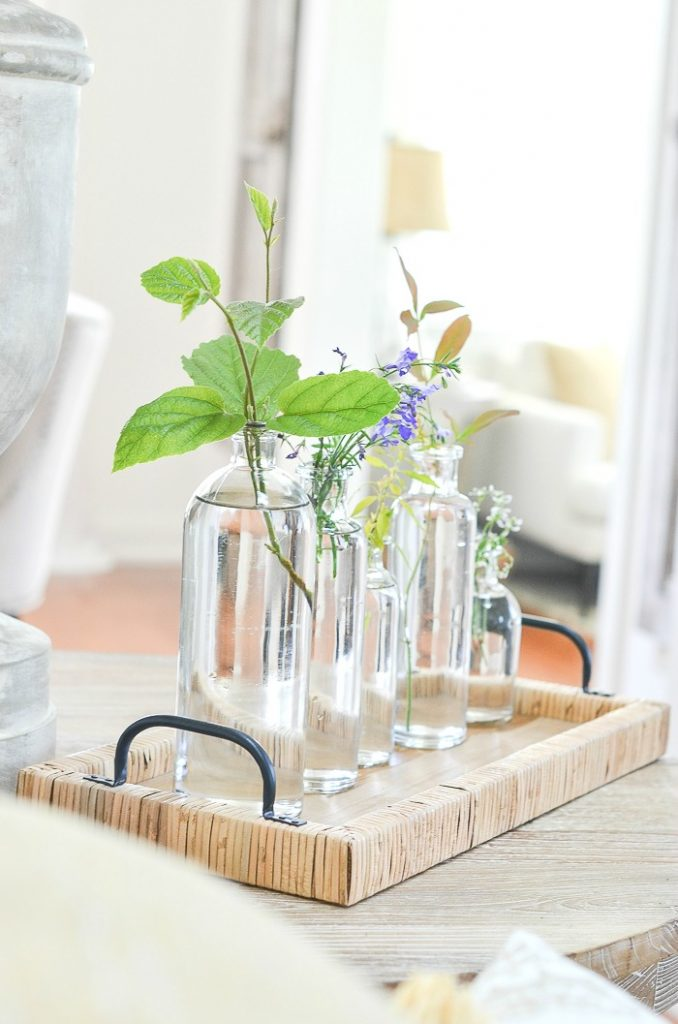 summer twigs, tendrils and flowers in a grouping of bottle vases for an easy summer centerpiece