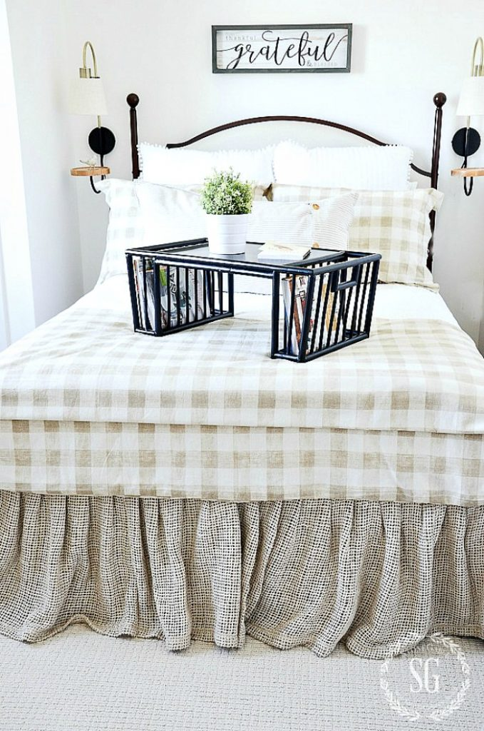 """guest room bed with a bed tray, two sconces and a sign above the bed that says, """"grateful'."""