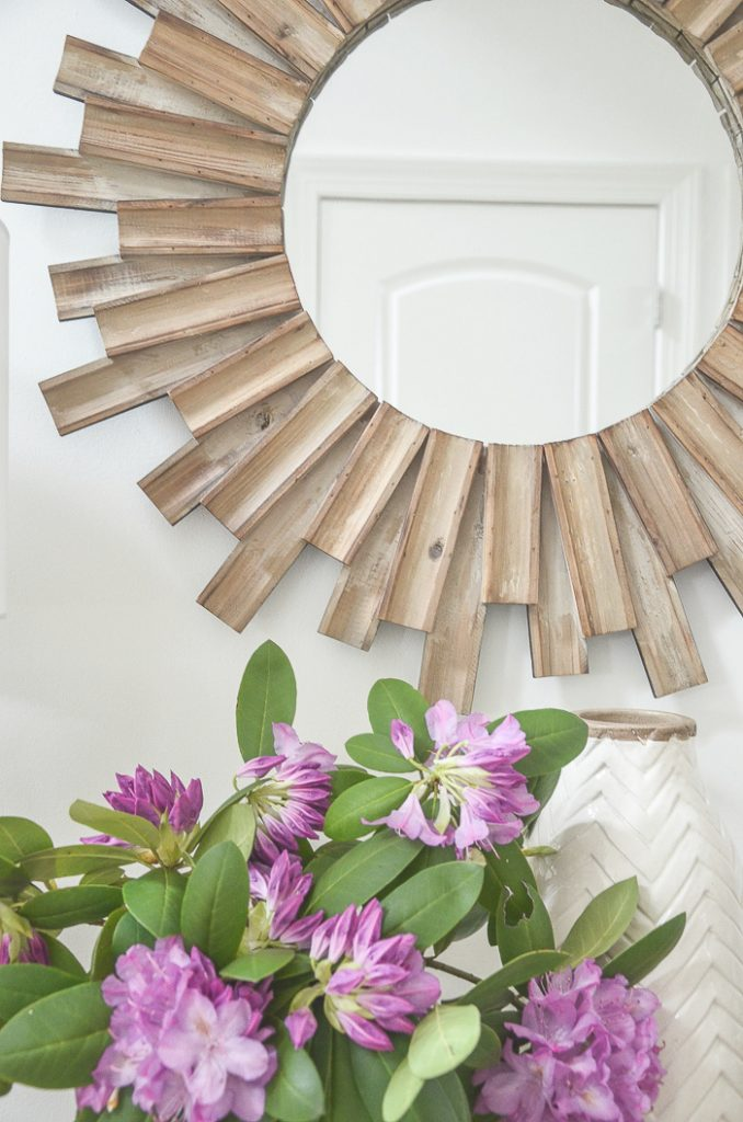 a wooden sunburst mirror above the foyer table