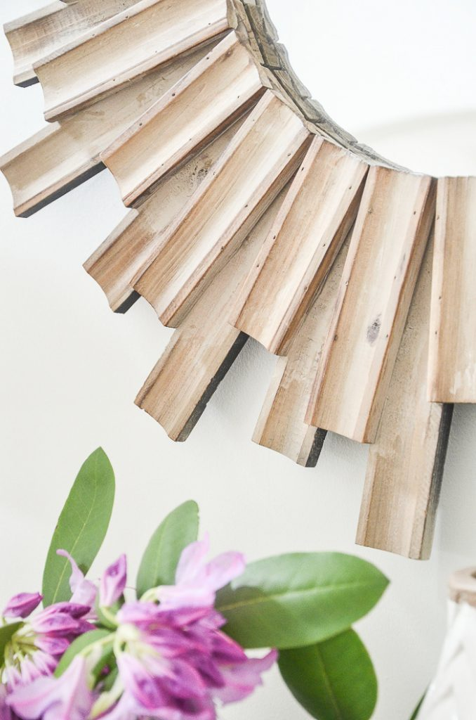 a wooden sunburst mirror above the foyer table. this mirror is made from wooden slats