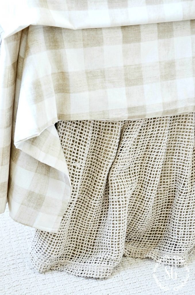 Raw linen bedskirt and pretty checked duvet cover on the bed.