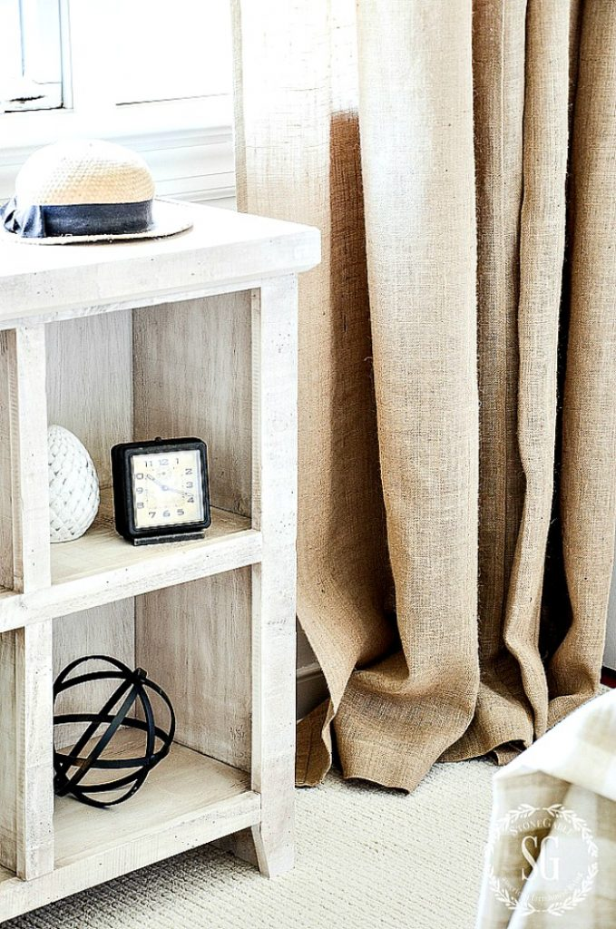 Burlap curtains and a small bookcase fill with decorative objects.
