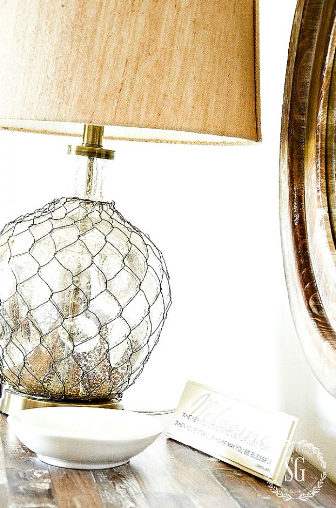 MERCURY GLASS LAMP COVERED WITH CHICKEN WIRE ON A DRESSER. WITH A SMALL BOWL IN FRONT OF IT