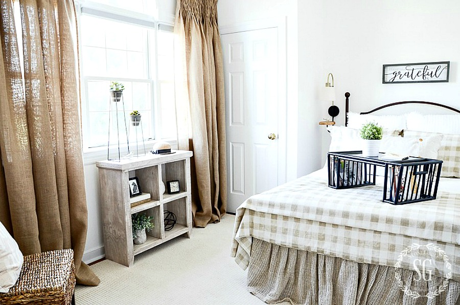 Neutral guest room with burlap curtains, a chair, small bookcase and an iron bed with checked linens. A black bed tray is on the bed.