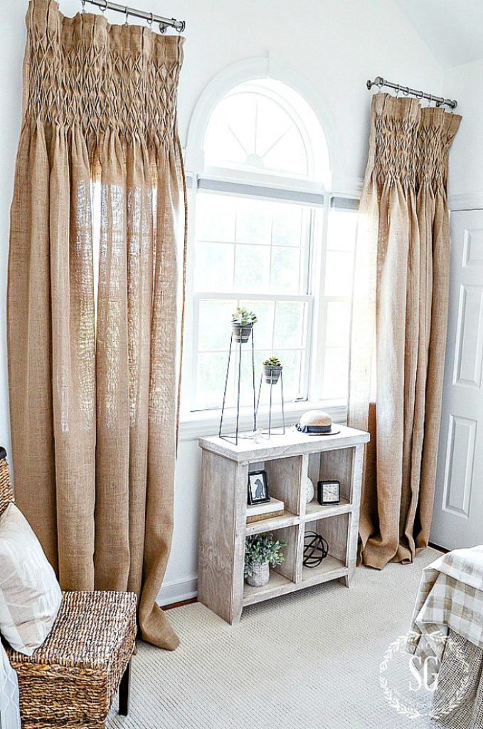 TALL WINDOW WITH SMOCKED-TOP BURLAP CURTAINS. UNDER THE WINDOW IS A SMALL BOOKCASE WITH DECORATIVE OBJECTS.