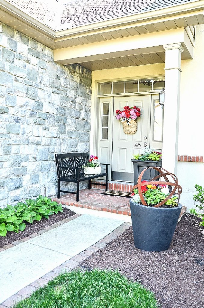 FRONT PORCH WITH BLACK BENCH AND PLANTERS WITH FLOWERS