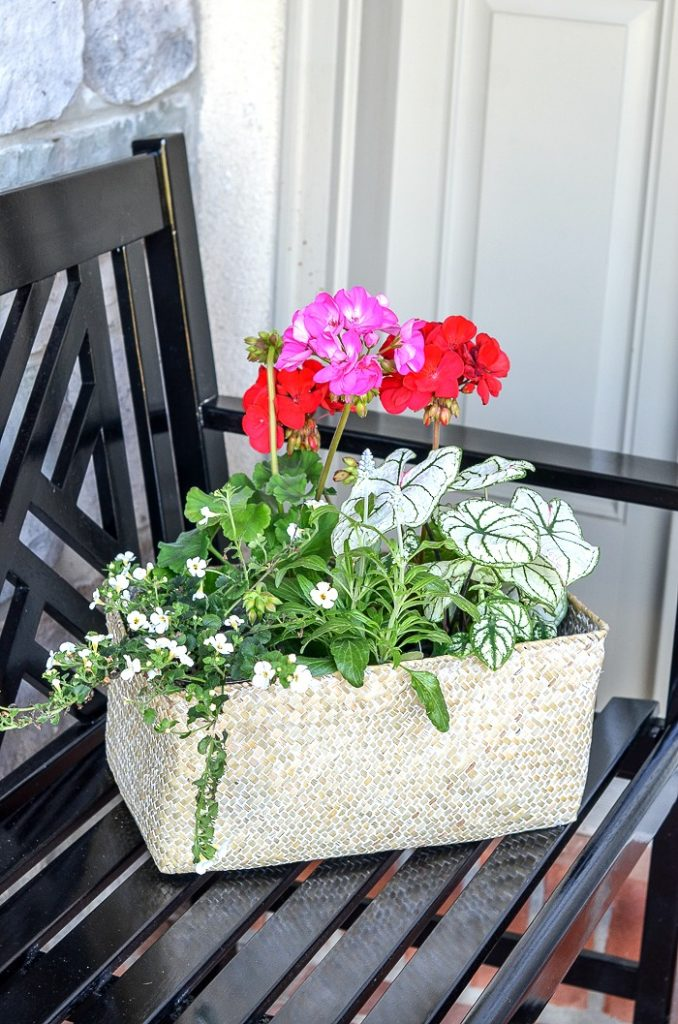 A BASKET OF FLOWERS ON A BENCH ON THE FRONT PORCH.