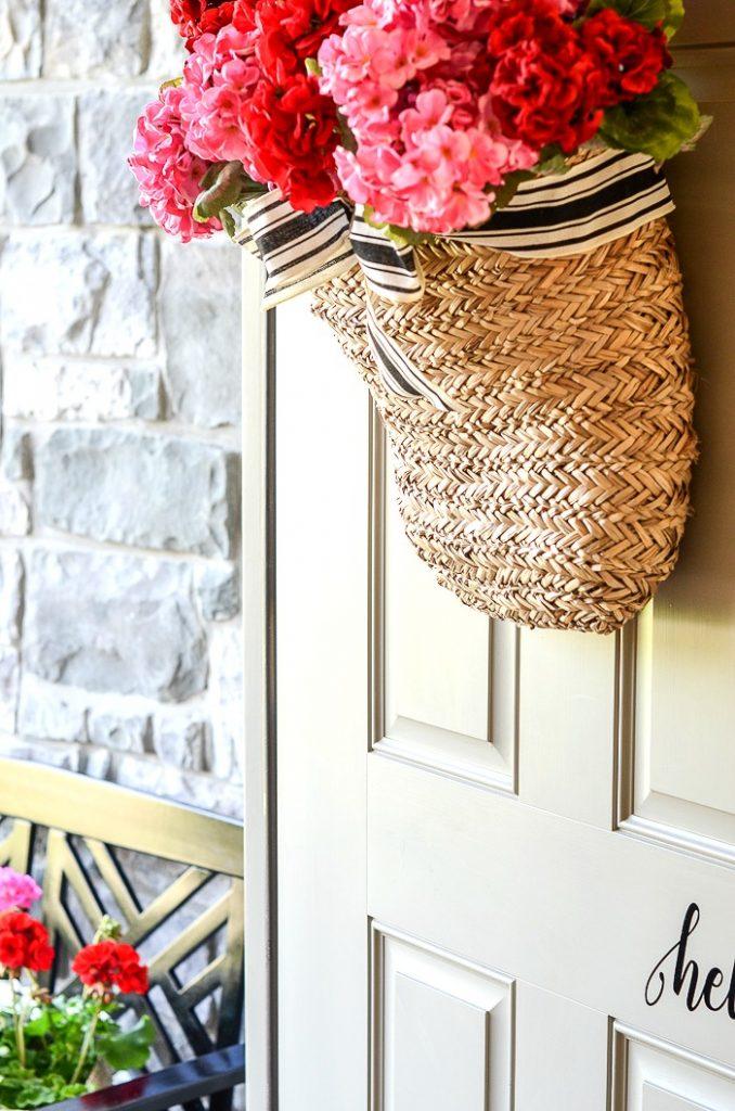 BASKET OF FLOWERS ON AN OPEN FRONT DOOR