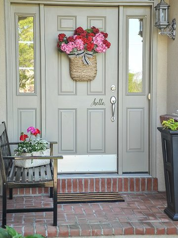 FRONT PORCH WITH HANGING BASKET OF FLOWERS ON THE FRONT DOOR