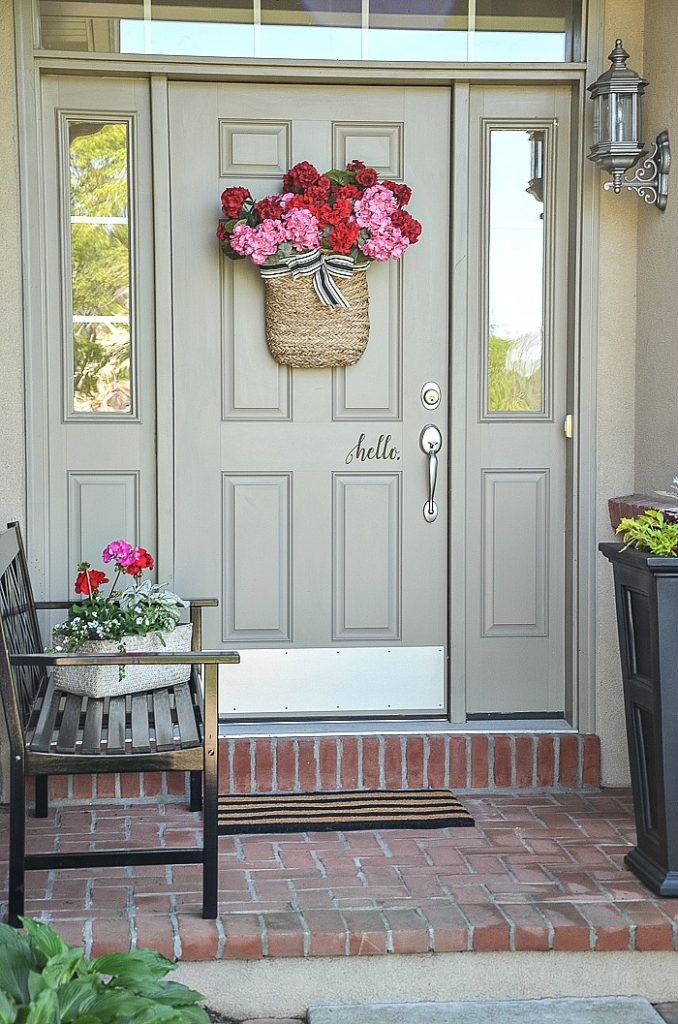 small front porch with bench and containers of flowers