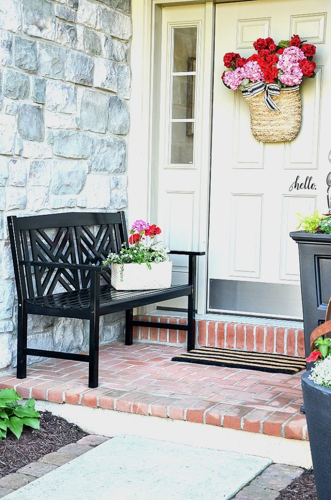 FRONT PORCH WITH BLACK BENCH AND LOTS OF FLOWERS