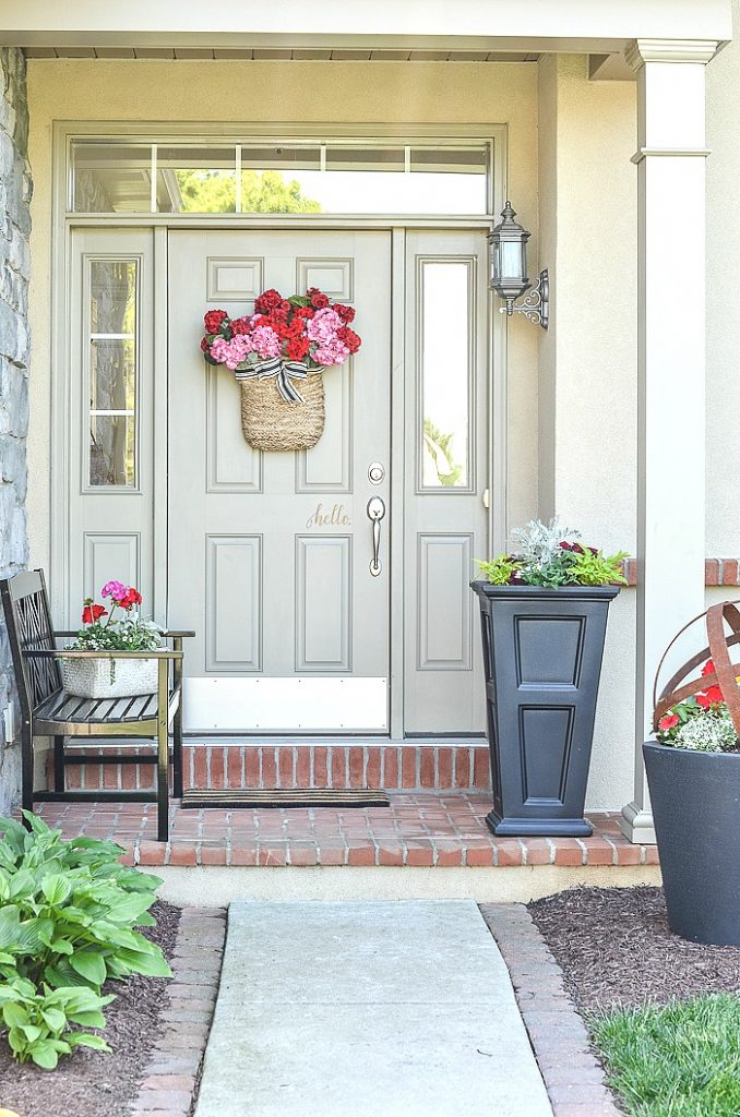 FRONT PORCH WITH BLACK BENCH AND PLANTERS FILLED WITH SUMMER FLOWERS