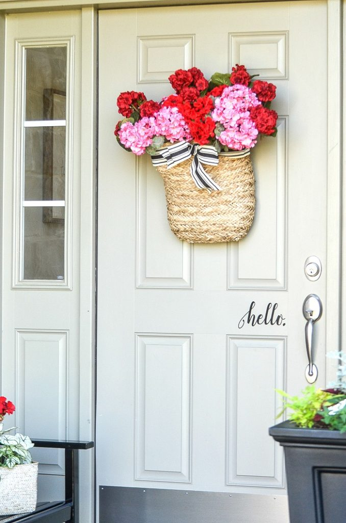 FRONT DOOR WITH A BASKET OF RED AND PINK GERANIUMS ON IT.