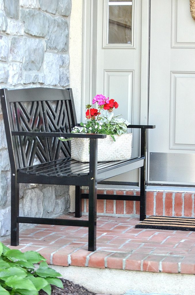 BENCH ON A SMALL FRONT PORCH WITH A BASKET OF FLOWERS SITTING ON IT