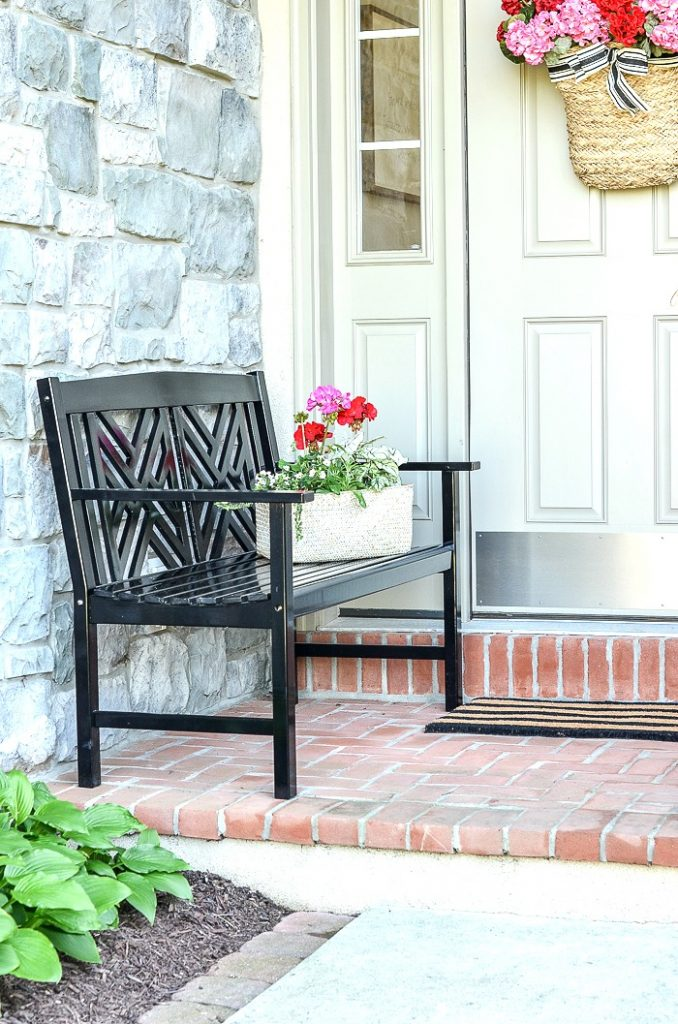 BLACK BENCH ON A SMALL FRONT PORCH