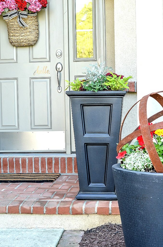 SMALL FRONT PORCH WITH BLACK PLANTERS. LOTS OF FLOWERS IN THE PLANTERS.