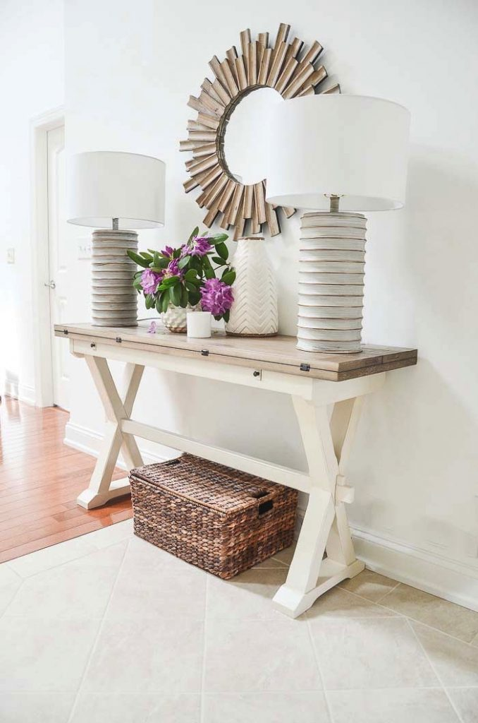 image of a foyer table, a mirror above it and a basket below it