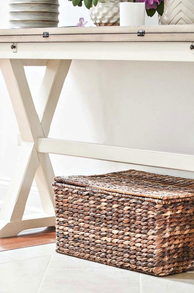 a basket below a foyer table. it stows things away neatly
