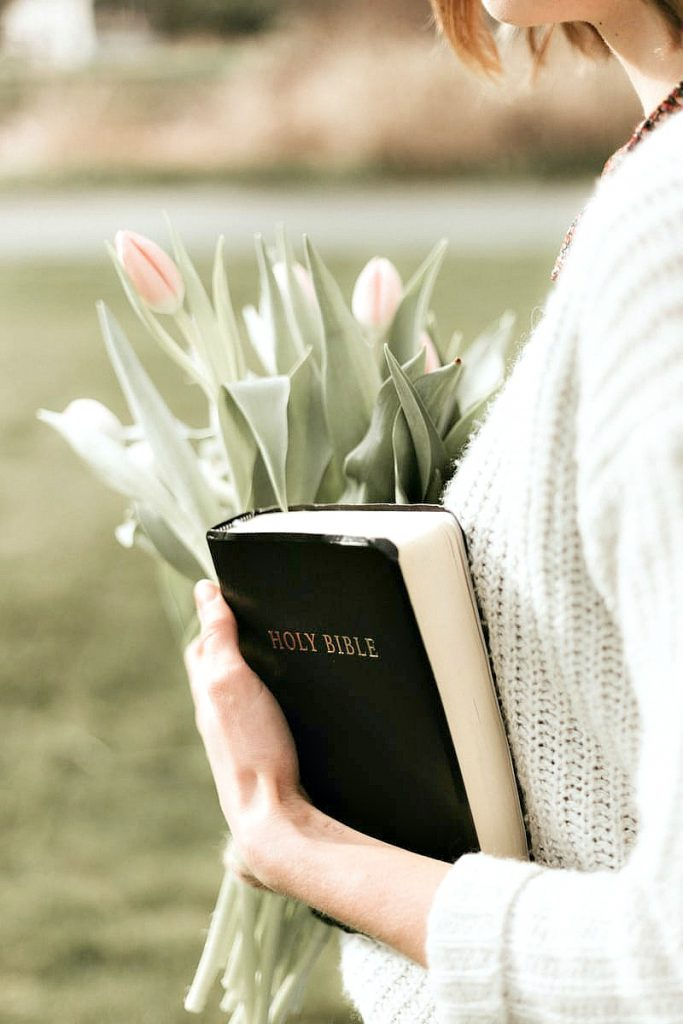 mom holding flower and a Bible