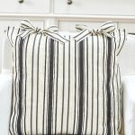 Pretty black and white pillow on a white chair