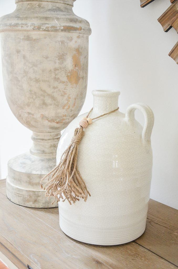 lamp and white jug with a twine tassel around its throat.